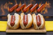 stock photo of hot dog  - Three hot dogs in buns with hot dogs cooking on a hot flaming barbecue grill - JPG