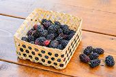 stock photo of mulberry  - Group of mulberries isolated on wood background - JPG