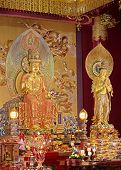 stock photo of altar  - altar with ornate statues of buddha inside temple - JPG