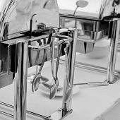 foto of tong  - Closeup Serving kitchen tongs with chafing dish - JPG