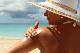 stock photo of body-lotion  - Young woman applying Suntan Lotion at the beach - JPG