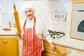 stock photo of kindness  - Kind elderly lady holding a rolling pin in the kitchen - JPG