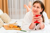 stock photo of bed breakfast  - thoughtful girl with notepad and breakfast in bed - JPG