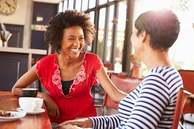 picture of bonding  - Two female friends talking at a coffee shop - JPG