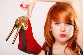 foto of stiletto  - Fashion girl with red high heel shoes stiletto boots with gold studs - JPG