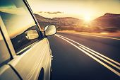 Road trip on sunset, car on the highway, conceptual image of escape and adventure travel, slow motio poster