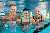 Happy mature man and old woman doing aqua aerobics with foam rollers in swimming pool. Senior couple poster
