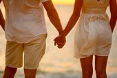 Romantic couple holding hands on beach sunset during travel. Closeup of happy woman and man together poster