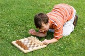 A boy is preparing for a chess game