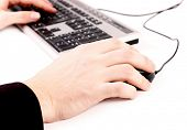 Image of hands pushing keys of a computer mouse and keyboard