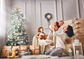 Merry Christmas and Happy Holidays! Cheerful mom and her cute daughters girls exchanging gifts. Pare poster