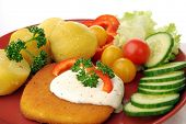 Serving of breaded cheese with potatoes and vegetable garnish