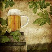 Glass of beer on old barrel and hop plant, grunge image