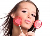 Young woman portrait with heart shaped lollipops. Isolated on white.