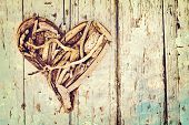 driftwood heart on a painted grunge wall with blue and white paint with pastel effect and space for