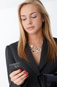 Portrait of young businesswoman using smart phone, texting.?