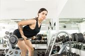 Determined Athlete Doing Bent Over Row Exercise With Barbell In Gym poster
