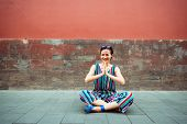 Young attractive chinese woman sitting in yoga pose and smiling outdoor over red wall, image toned.  poster