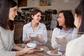 Four female friends relaxing over coffee at a coffee shop poster