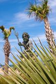 King Neptune Statue And Tropical Foliage