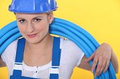 A tradeswoman with tubes coiled around her neck