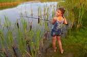 image of happy kids  - pretty young smiling girl fishing with long rod  on river outside in summer sunshine - JPG
