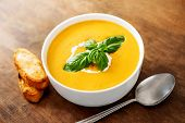 Bowl Of Squash Soup With Basil Leaf On Wood Table. Pumpkin Soup Served In A Bowl, Top View poster