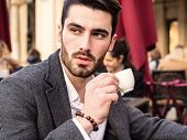 Handsome Young Man Drinking Espresso Coffee, Wearing Elegant Coat Posing At Table Outside On Elegant poster