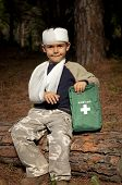 foto of sling bag  - First Aid treatment given to a young boy in the forest showing an arm sling and a head injury - JPG