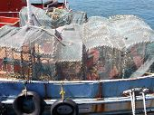foto of lobster boat  - Side on view of a boat carrying lobster or crayfish nets docked in Kalk Bay harbour near Fish Hoek  - JPG