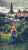 Retro Style Redhead Teenage Girl Looking Out Over Glasgow Cathedral And Skyline With A Rainy Sky poster