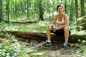 Mature woman runner resting in woods.