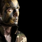 picture of special forces  - portrait of young soldier face with jungle camouflage against a black background - JPG