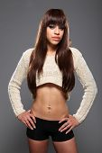 picture of pierced belly button  - Sexy young mixed race fashion model woman with beautiful green eyes showing flat stomach and long brown hair wearing short knitted top and black boy shorts - JPG