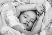 Sleepy Baby In Colorful Blanket. Child Sleep In Bed. Trust And Tenderness. Childhood And Happiness.  poster