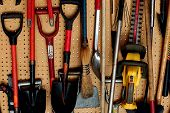 image of power-shovel  - neatly organized tools on the wall in the garage