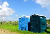 stock photo of outhouses  - Green and blue outhouses near a river - JPG
