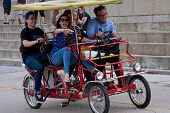 Young Adults Pedal A Four-wheeled Cycle Along Lake Shore Drive