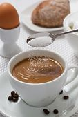 Pouring sugar on coffee cup