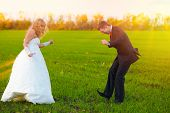 bride and groom sunlight dancing merrily in green field, couple,