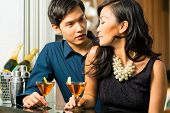 Asian man and woman in flirting intimately at bar drinking cocktails