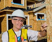 stock photo of 2x4  - Carpenter with red shirt and white hardhat building a roof of a house at a construction site - JPG