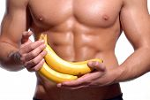 Shaped and healthy body man holding a fresh bananas,shaped abdominal,