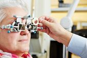 Senior woman with astigmatism and trial frame at the optician