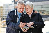 Senior couple as tourists with map and smartphone in a city