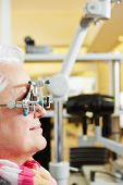 Senior Woman with trial frame gets examination at ophthalmologist