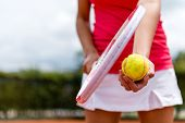 Female tennis player holding racket and a ball