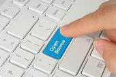 stock photo of open-source  - Hand pushing blue open source keyboard button - JPG