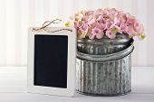 foto of hydrangea  - Pink hydrangea flowers in a metal vase on vintage background with empty blackboard for copy space - JPG