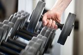 stock photo of weight-lifting  - close up of man holding weight in gym - JPG